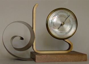 Scroll and Barometer. 6.75 inches in height, wood, gray metal, steel. Circa 1937.